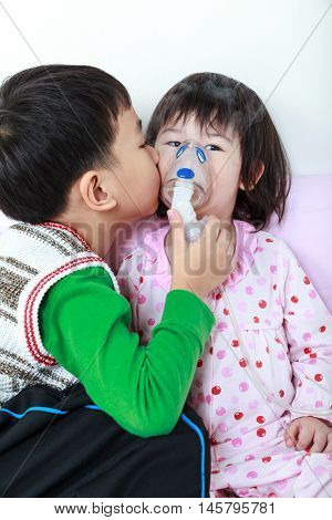 Asian child was bronchitis and crying. Loving brother take care his sister with asthma problems making inhalation by mask at hospital. Brother kiss on cheek his sister loving and bonding of sibling.