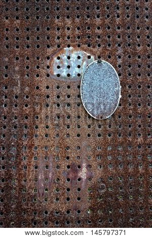 Rusted metal with holes and a broken metal tag.