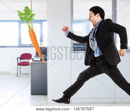 Businessman trying to take a carrot. Motivation concept
