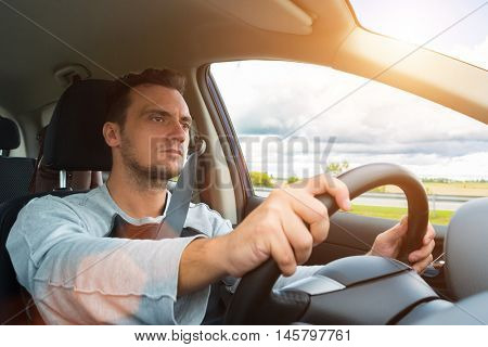 Detail of a man driving his car. Bright light effect
