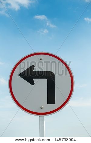 Turn left traffic sign on skies background.