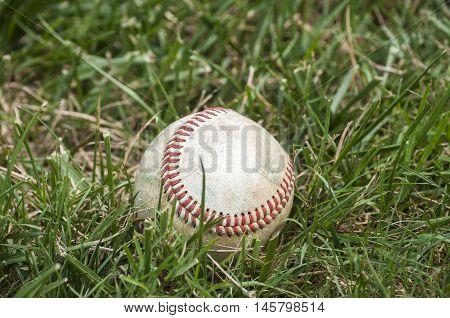 Used weathered grunge baseball ball on green grass background