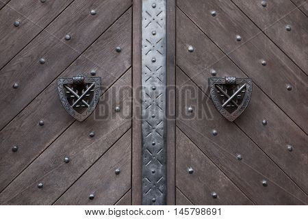 Doorknockers on the wooden gate fixed with rivets in Kokorin Castle in Central Bohemia, Czech Republic.