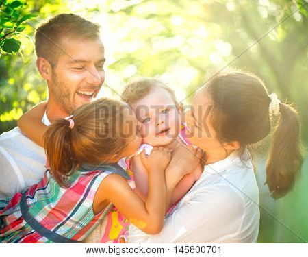 Happy joyful young family with children. Father, mother and little kids having fun outdoors in orchard garden, playing together in autumn park. Mom, Dad, kids laughing and hugging, enjoying nature