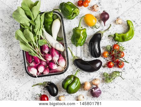 Fresh vegetables - radishes tomatoes peppers onions garlic eggplant on a light background top view. Raw ingredients for cooking