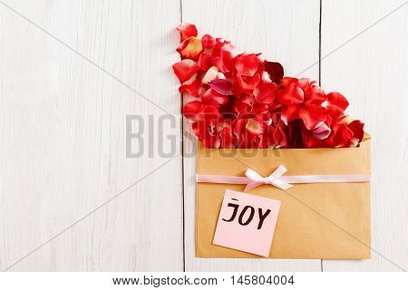 Floral present with rose petals and joy text, flat lay, copy space. Beautiful greeting composition made from red flower bloom and brown kraft envelope on white wooden background