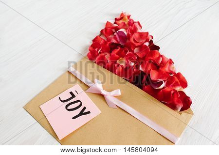 Floral present with rose petals and joy text. Beautiful greeting composition made from red flower bloom and brown kraft envelope on white wooden background
