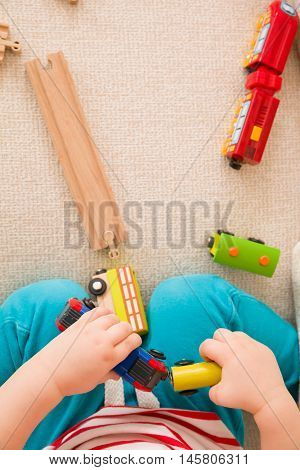 Closeup of child's hands playing with wooden train toys and railway. Top view. Toddler boy sitting and playing with railroad indoors. Developing activities for toddlers in daycare and nursery.