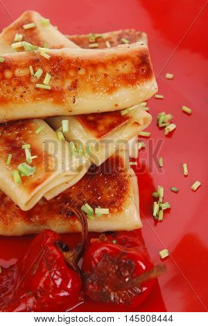 russian food - meat wrapped in a pancake with red hot pepper and pickled mushrooms served on red plate isolated over white background