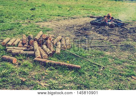 Rustic bonfire and log of wood for burning, vintage photo.