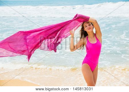 Sport girl-teenager in a pink bathing suit on background of ocean.