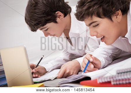 Classmates doing homework together at home, resolving difficult task, preparation to exams, with pleasure studying at school