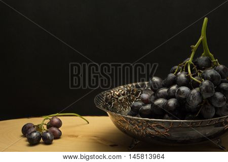 Antique Fruit Bowl With Cluster Of Grapes, On Wooden Surface And Black Background