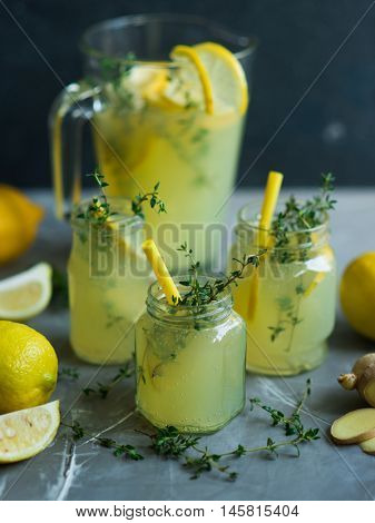 Lemonade drink. Lemonade in the jug and glass jars with lemons, ginger and thyme