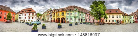 Panorama of the Sighisoara Citadel Square or Fortress Square. Colourful medieval houses with dramatic skies. Panoramic montage from 11 HDR images