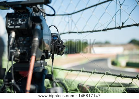 Television camera on motor sport circuit selective focus detail on handle and track out of focus in background