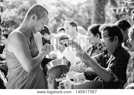 Prachuapkhirikhan Thailand - November 16 2015 : Unidentified man of Buddhist offer foods to a monk for make merit in a Religious ceremony,black and white color picture style