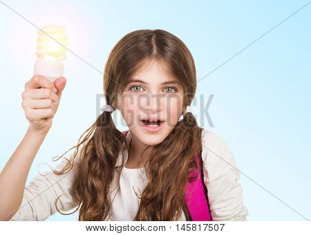 Portrait of a clever school girl with new idea, holding glowing lamp in hands, create a solution and resolve a problem concept, back to school