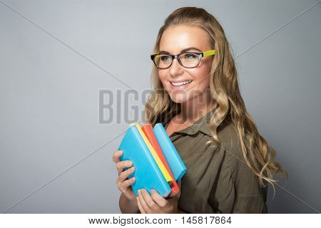 Cute student girl portrait, wearing grasses and standing with books over gray background, ready to new study season, enjoying education in a college