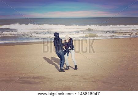 Two teenagers playing in winter in a beach of Mar del Plata Argentina