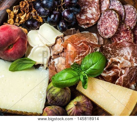 Italian antipasti snack for wine. Prosciutto di Parma, salami, cheese variety, figs, grapes, peach, walnuts and fresh basil leaves over wooden serving tray background, top view