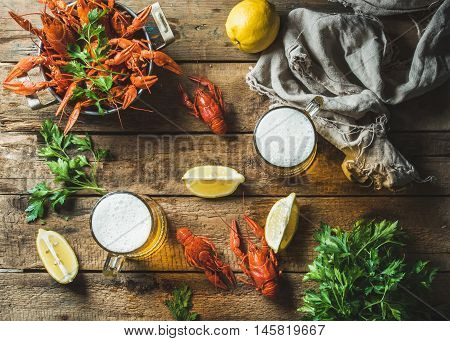 Two pints of wheat beer and boiled crayfish with lemon and parsley over old wooden rustic background, top view, horizontal composition