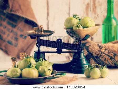 authentic Spanish farmhouse scene showing freshly picked organic green tomatoes in green scales on an old wooden table soft window light. filter added for mood