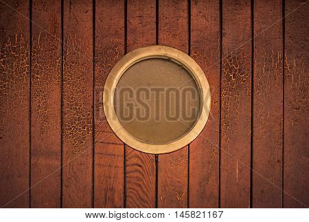 Round window on wooden wall - Background with a wall made of wooden planks and a small round window in the middle.