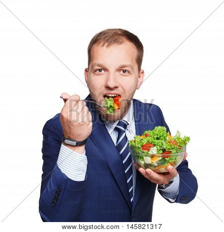 Healthy food and diet concept. Young businessman holds and eats fresh vegetable salad meal isolated on white background. Modern dieting and weight loss nutrition for busy men.