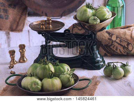 authentic country farmhouse scene showing freshly picked organic green tomatoes in green scales on an old wooden table soft window light. bottom blur for copy space