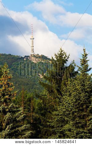 Broadcasting tower on a mountain top viewed against a cloudy blue sky between evergreen conifers in Sofia Bulgaria in a communications concept