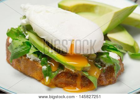 Poached egg on piece of bread with avocado and arugula close up on white plate