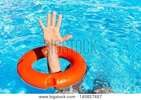 Arm with hand through orange buoy in blue swimming pool