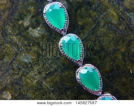 Female bracelet on a dark background decoration bijouterie gift accessory material silver female rock green emerald sapphire
