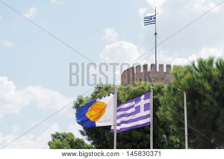 Thessaloniki, Greece municipal and Greek flag. The flag is waving before the White Tower, the landmark of the city and depicts Alexander the Great at ancient coin.