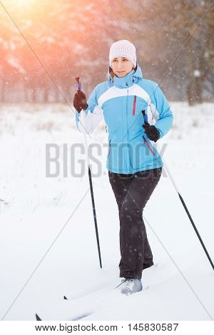 Young woman cross-country skiing in winter park.