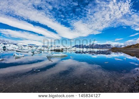 Ice lagoon in Iceland. Beautiful summer morning in the ocean bay with ice floes. Stratus, diverging fan, reflected in the mirrored surface of the water