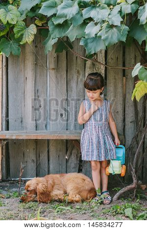country girl with her dog under vine. girl playing with her dog. wooden background.