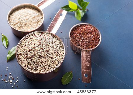 Mixed raw quinoa, South American grain, in copper measuring cups with bay laurel leaves on blue background. Healthy and gluten free food. Copy space.