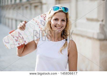 Skateboarder girl posing at city