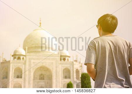 Young traveler looking and walking towards Taj Mahal in Agra India.