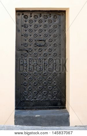 Old black metal door with forged flowers background