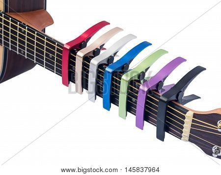 Colorful Capo On Guitar Fingerboard, White Background , Close Up