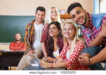 Young Students Group Using Tablet Computer, Mixed Race People Smiling Looking To Camera, Sit At Desk University Classroom