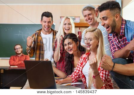 Young Excited Students Group Using Laptop Computer, Mixed Race People Happy Smiling Laugh, Sit At Desk University Classroom