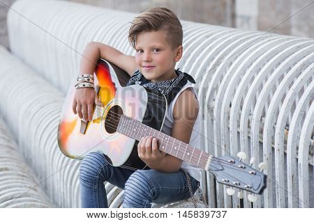 Stylish Little Boy Learns To Play The Guitar . He Was Good At It .