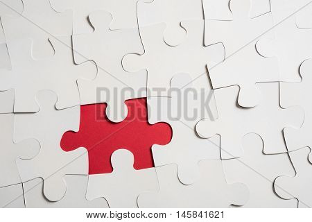 High angle view of one piece missing from white jigsaw puzzle. White jigsaw puzzle spread over red background. Top view of red missing piece of the white puzzle. Concept of business problem solving.