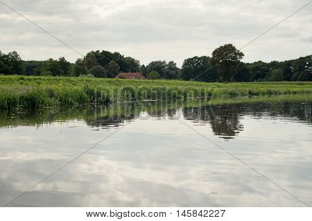 Dutch River De Berkel With Dyke And Farm. Achterhoek. Gelderland. The Netherlands.