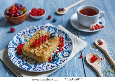 Sweet breakfast with pastry pie and berries - red currant and bluberries. Beautiful food served at blue rustic wooden table, cake dessert at ethnic porcelain plate, tea cup.