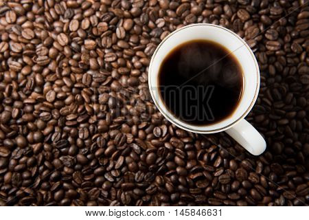 White coffee cup on coffee seeds background